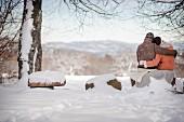 Mann und Frau sitzen Arm in Arm und blicken auf verschneite Landschaft