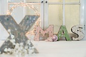 Shabby-chic ornamental letters spelling XMAS in front of window