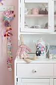 Rabbit soft toy on romantic, white dresser next to hair clips clipped on ribbon hung on wall in girl's bedroom