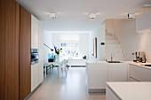 Große offene Küche mit weißem Boden und Esstisch