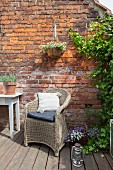 Wicker armchair on terrace in front of ivy growing on brick wall