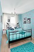 Blaues Schlafzimmer mit Metallbett und Blümchentapete