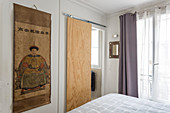 Plywood sliding door next to Chinese wall hanging