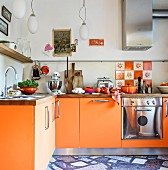 Orange base units and tiles in kitchen without wall units