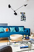 Designer lamp on wall above blue sofa and delicate coffee table
