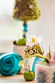 Hellebore flowers, green apple, turquoise felt flower and small tree ornament in blurred background