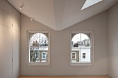 Two arched windows in modernised bare room with floor-to-ceiling, simple fitted cupboards