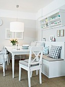A white dining area in a country house-style with a comfortable bench and a wall shelf