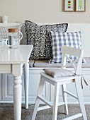 A white highchair with a cushion at a dining table and a bench with various cushions in a country house-style room