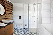Rustic log-cabin wall, bathtub and glazed shower cubicle in bathroom