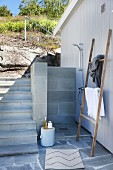 Outdoor shower on white wooden wall next to steps and retaining wall in a hillside garden