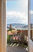 Blick durch offene Balkontür auf nostalgischen Bistrotisch mit Obstschale und Vintage Stuhl