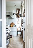 View into traditional kitchen with white kitchen counter and vintage-style candle chandelier