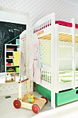 White bunk beds and push-along cart in front of full-length mirror in children's bedroom