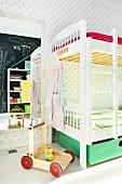 Kinderzimmer mit weißem Etagenbett und Lauflernwagen vor Wandspiegel