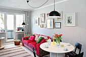 Round white dining table, red sofa and gallery of pictures in living room