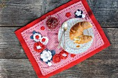 Breakfast on red and white hand-made place mat with crocheted flowers