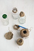Balls of string, crochet hook and glass bottles with crocheted trim