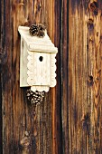 Traditional bird nesting box decorated with ornamental trim and pine cones hung on board wall