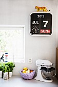Herbs, fruit basket and mixer on kitchen counter below calendar clock on white-tiled wall