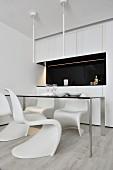 weiße Klassiker-Schalenstühle um filigranen Tisch vor Küchenzeile mit schwarzem Spritzschutz