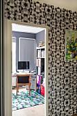 Blick vom Flur mit grafisch gemusterter Tapete ins Büro