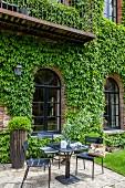 Sitzplatz vor mit wildem Wein bewachsenen Backsteinhaus
