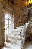 Curved stone staircase against rustic brick wall