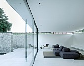 Minimalist designer furnishings in lounge area of white luxury apartment with glass wall, terrace and stone wall