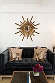 Scatter cushions with stag motifs on black velvet sofa below sunburst mirror on white wall