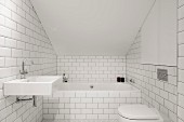 Bathtub and toilet in white-tiled attic bathroom