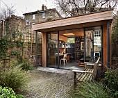 Blick von der Terrasse in modernen, holzverkleideten Anbau mit Schreibtisch und Bücherregal