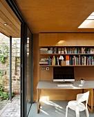 Schreibtisch mit Computer in modernem Anbau mit Holzverkleidung, Oberlicht und geöffneter Terrassentür