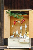 Modern nativity scene arrangement of white-painted nativity set figurines, old Christmas tree decorations, mercury silver candlesticks and green fir branches in vintage dolls'-house cabinet