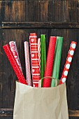 Rolls of red and green gift wrap in paper bag