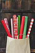 Geschenkpapierrollen in Rot und Grün in einer Papiertüte