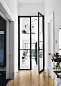 Hallway with open, black glass double door and a view of the living area and gallery