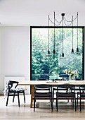 Dining area with black chairs around precious wood table under designer pendant lights in front of floor-to-ceiling window