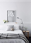 Double bed with bedspread and pillow in front of bed head with storage space