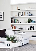 White coffee table and sofa in front of an open shelf
