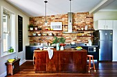 Kitchen with brick wall, kitchen island and wooden floor