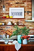 Vases on the kitchen island in front of a brick wall