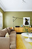 Light upholstered sofa and tulip table in olive green living room with retro flair