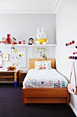 Wooden bed, white shelf and colorful classic wall wardrobe in the children's room