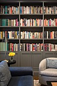 Sofa and armchairs in front of grey bookcase