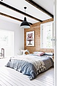 Double bed with throw in front of wooden wall in bedroom with wooden beam ceiling