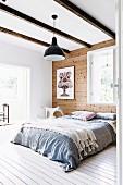 Doppelbett mit Überwurf vor Holzwand in Schlafzimmer mit Holzbalkendecke