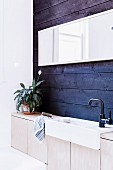 Row of vanities with wooden base cabinets against blue wall paneling