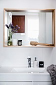 White washstand, above wall mirror with wooden frame as a shelf with bathroom accessories