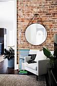 Runder Wandspiegel an Ziegelwand, darunter weisser Sessel in renovierter Altbauwohnung